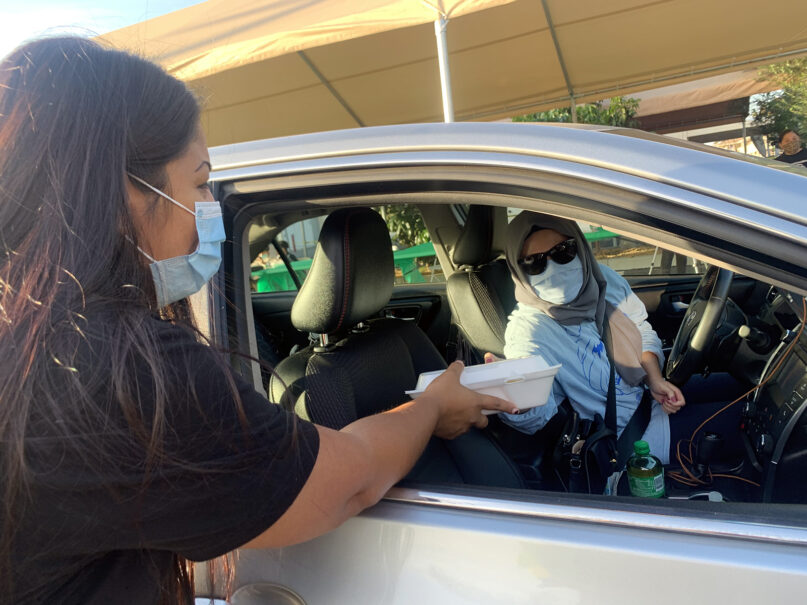 Carolyn Torres hands out a box of halal tacos at a Taco Trucks At Every Mosque voter registration event at the Islamic Center of Santa Ana, Oct. 18, 2020, in Santa Ana, California. Photo courtesy of Latino & Muslim Unity