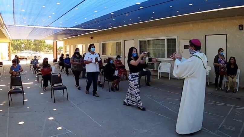 Congregants participate in the presentation of the gifts to the Most Rev. Ángel Velandia, right, at the beginning of the Eucharist during an outdoor morning service at Mision Cristo Rey in southern California on Sept. 27, 2020. Video screengrab