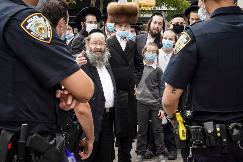 Members of the Orthodox Jewish community speak with New York police officers on Oct. 7, 2020, in the Borough Park neighborhood of New York's Brooklyn borough. (AP Photo/John Minchillo)