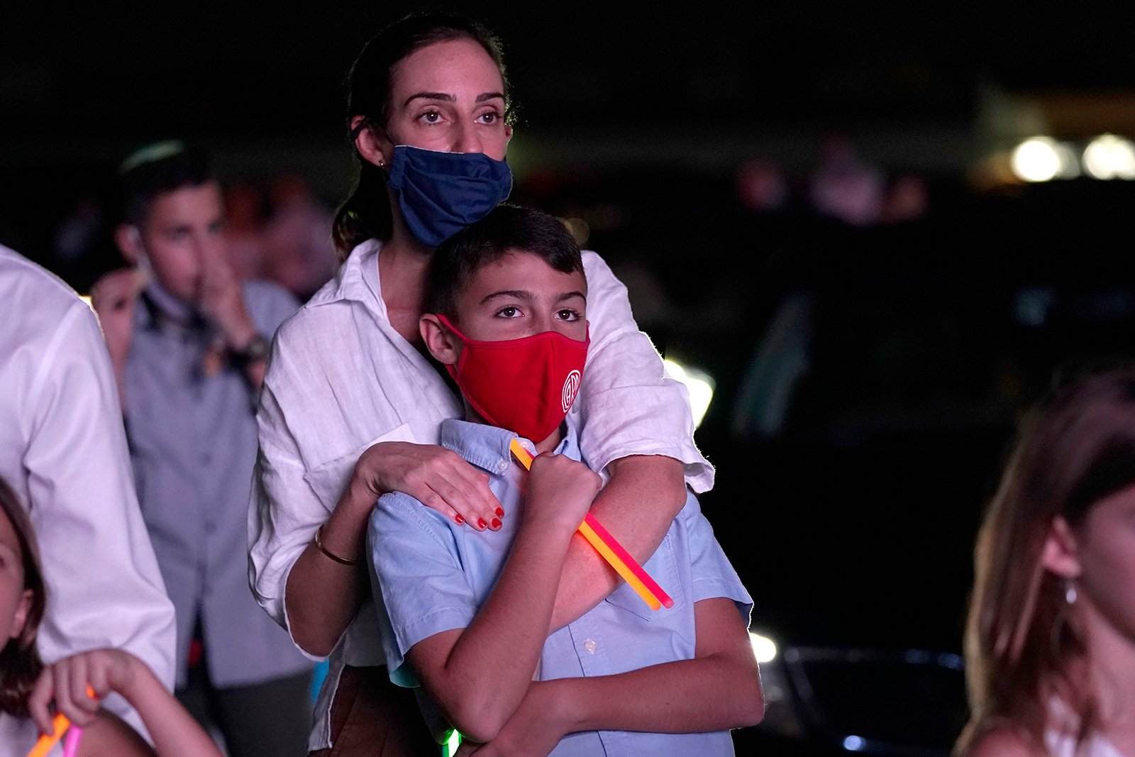 Dana Herseovici stands with her son Tomas during an outdoor Yom Kippur service hosted by the Aventura Turnberry Jewish Center, during the coronavirus pandemic, Sept. 28, 2020, at the Dezerland Park drive-in theatre in North Miami, Florida. (AP Photo/Lynne Sladky)