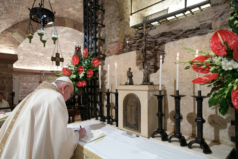 Pope Francis signs his new encyclical, 'Fratelli tutti', during a visit to Assisi, Italy, on Saturday, Oct. 3, 2020. In his first official trip outside Rome since the pandemic struck Italy, the pope celebrated Mass at the tomb of his namesake, St. Francis of Assisi. 'Fratelli tutti' the encyclical's opening words, means 'All brothers' in Italian. The phrase is taken from the writings of St. Francis, one of the major inspirations for Pope Francis' third encyclical, on fraternity and social friendship. The text was released Oct. 4, St. Francis' feast day. Photo by Vatican Media