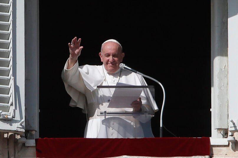 Pope Francis waves at the end of his Angelus noon prayer from the window of his studio overlooking St. Peter's Square, at the Vatican, Oct. 25, 2020. (AP Photo/Alessandra Tarantino)