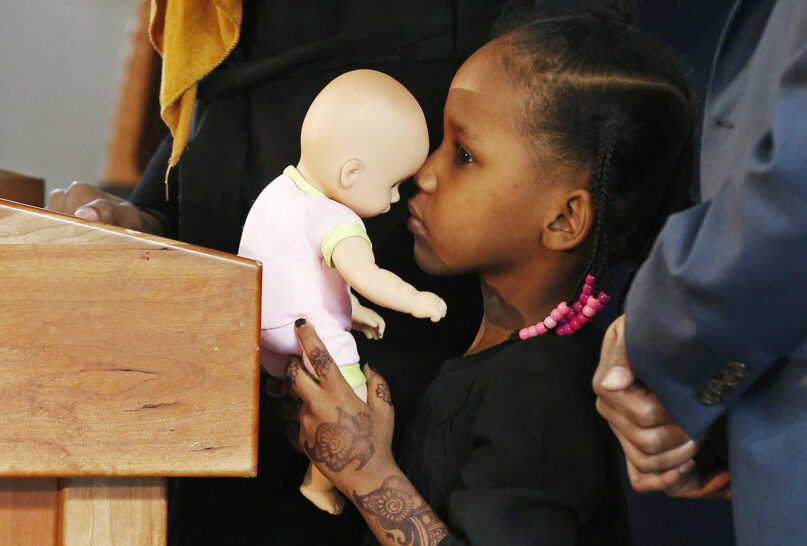 In this Feb. 3, 2017, file photo, 4-year-old Somali refugee Mushkaad Abdi holds her doll as her mother, Samira Dahir, talks during a Minneapolis news conference one day after she was reunited with her family. Her trip from Uganda to Minnesota was held up by President Donald Trump's Jan. 27, 2017, order barring refugees from seven predominantly Muslim nations. (AP Photo/Jim Mone, File)
