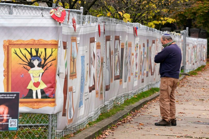A man observes a moment of silent reflection on the sidewalk outside the Tree of Life synagogue in Pittsburgh on Oct. 27, 2020, the second anniversary of the shooting at the synagogue that killed 11 worshippers. (AP Photo/Gene J. Puskar)