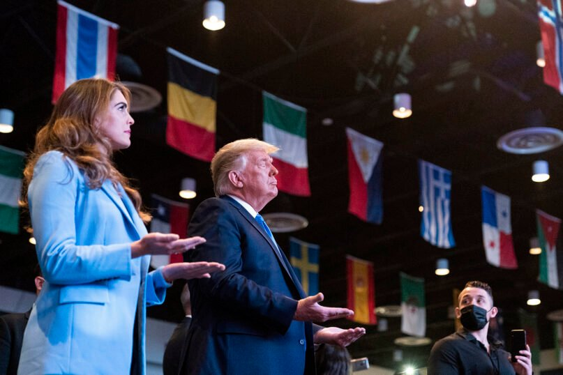 President Donald Trump closes his eyes as he accepts blessings as he attends church at International Church of Las Vegas, Sunday, Oct. 18, 2020, in Las Vegas, Nev. Counselor to the President Hope Hicks is at left. (AP Photo/Alex Brandon)