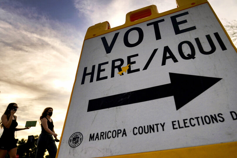 Voters deliver their ballots to a polling station Nov. 3, 2020, in Tempe, Arizona. (AP Photo/Matt York)