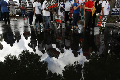 People carrying signs supporting voting rights are reflected in a puddle as they arrive at an early voting center at Model City Branch Library, as part of a