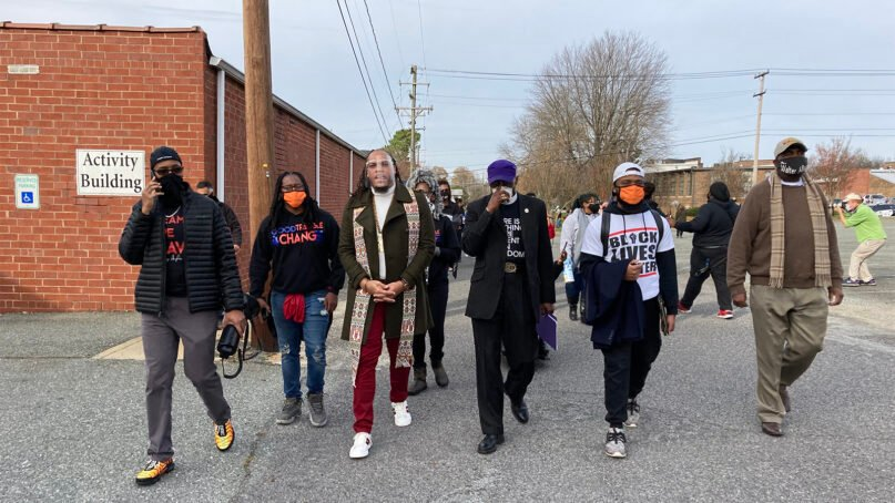 The Rev. Greg Drumwright, center left, leads a march for criminal justice reform in Graham, North Carolina, on Sunday, Nov. 29, 2020. RNS photo by Yonat Shimron