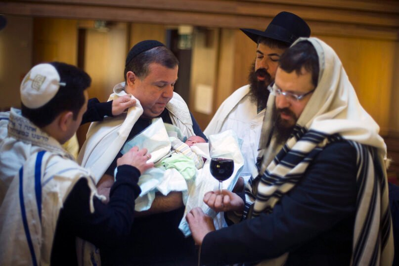 Eight-day-old Jonathan is surrounded by relatives and Rabbi Yehuda Teichtal, right, and mohel doctor Yacov Gassinovitch, second right, after the boy's circumcision at  a synagogue in Berlin on Oct. 29, 2012. (AP Photo/Markus Schreiber)