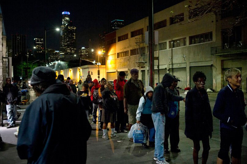 In this Sept. 19, 2017, file photo, people line up for free food being given out in an area of downtown Los Angeles known as Skid Row. (AP Photo/Jae C. Hong)