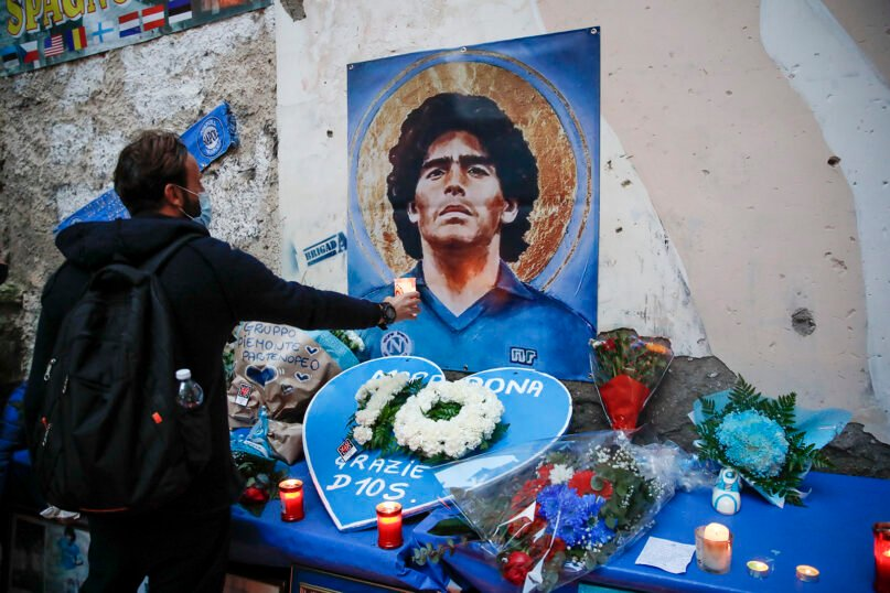 A man holds a candle as people gather to honor soccer legend Diego Maradona, at the popular