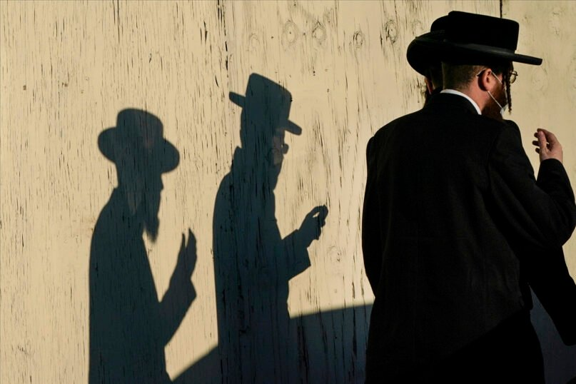 Men walk past the Yetev Lev temple on Nov. 23, 2020, in the Brooklyn borough of New York. (AP Photo/Frank Franklin II)