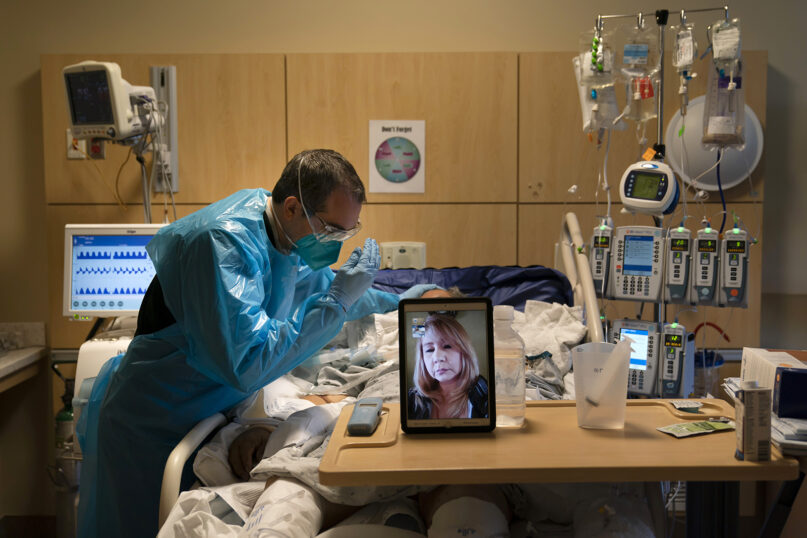 Chaplain Kevin Deegan prays for COVID-19 patient Pedro Basulto while on a video call with the patient's daughter, Grace, at Providence Holy Cross Medical Center in the Mission Hills section of Los Angeles, Thursday, Nov. 19, 2020.