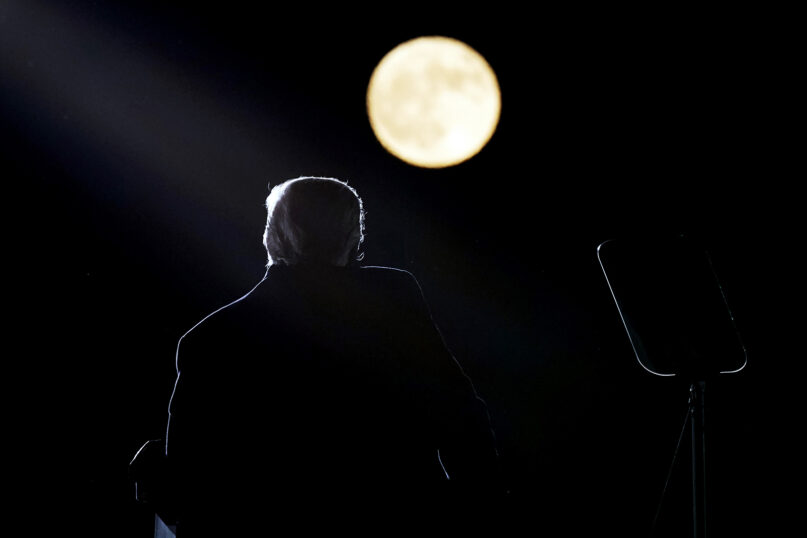 With a full moon in the background, President Donald Trump speaks at a campaign rally at Pittsburgh-Butler Regional Airport, Saturday, Oct. 31, 2020, in Butler, Pennsylvania. (AP Photo/Alex Brandon)