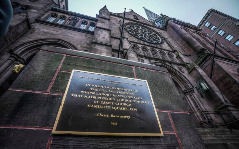 A plaque sits at the steps of St. James Episcopal Church on Dec. 4, 2020, in New York's Upper East Side neighborhood, acknowledging the church's wealth created with slave labor. (AP Photo/Bebeto Matthews)