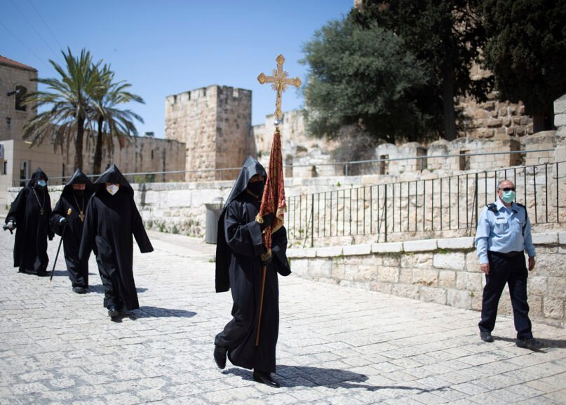 Armenian clergymen with face masks and gloves walk toward the Church of the Holy Sepulchre, traditionally believed by many Christians to be the site of the crucifixion and burial of Jesus Christ, in Jerusalem's Old City, after the traditional Holy Fire ceremony was called off due to coronavirus restrictions, April 18, 2020. A few clergymen marked the Holy Fire ceremony as the coronavirus pandemic prevented thousands of Orthodox Christians from participating in one of their most ancient and mysterious rituals at the Jerusalem church marking the site of Jesus' tomb. (AP Photo/Ariel Schalit)