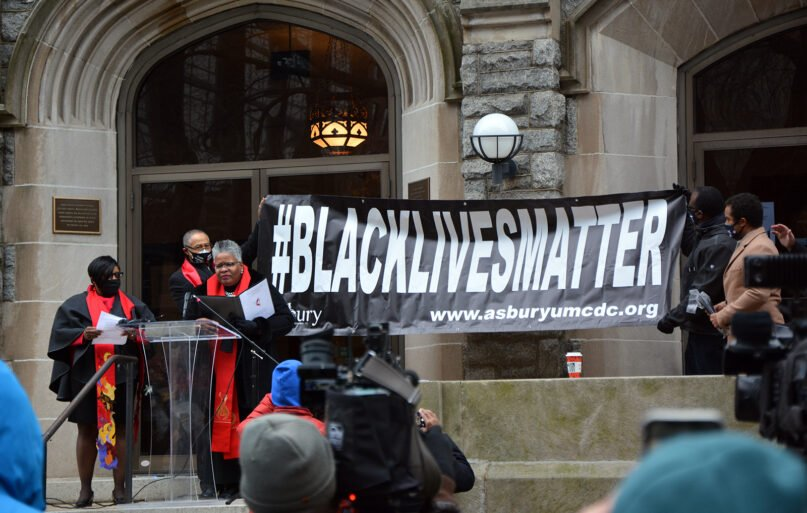 Bishop LaTrelle Easterling, third from left, speaks at the unveiling of a new Black Lives Matter sign at Asbury United Methodist Church, Friday, Dec. 18, 2020, in Washington. The previous sign was destroyed. RNS photo by Jack Jenkins