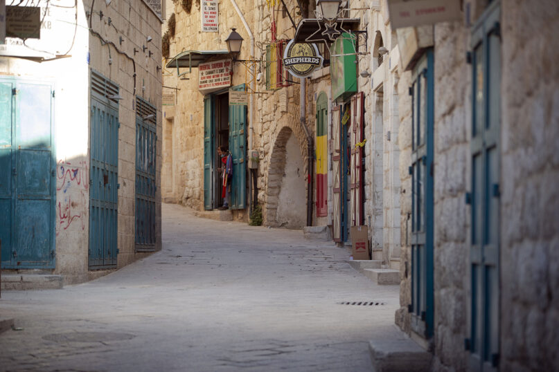 A vendor stands in front of his shop near the Church of the Nativity, traditionally believed to be the birthplace of Jesus Christ, in the West Bank City of Bethlehem, Monday, Nov. 23, 2020. Normally packed with tourists from around the world at this time of year, Bethlehem resembles a ghost town – with hotels, restaurants and souvenir shops shuttered by the pandemic. (AP Photo/Majdi Mohammed)