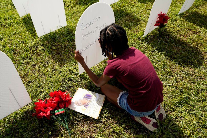 In this Nov. 24, 2020, file photo, Kyla Harris, 10, writes a tribute to her grandmother Patsy Gilreath Moore, who died at age 79 of COVID-19, at a symbolic cemetery created to remember and honor lives lost to COVID-19 in the Liberty City neighborhood of Miami. (AP Photo/Lynne Sladky)