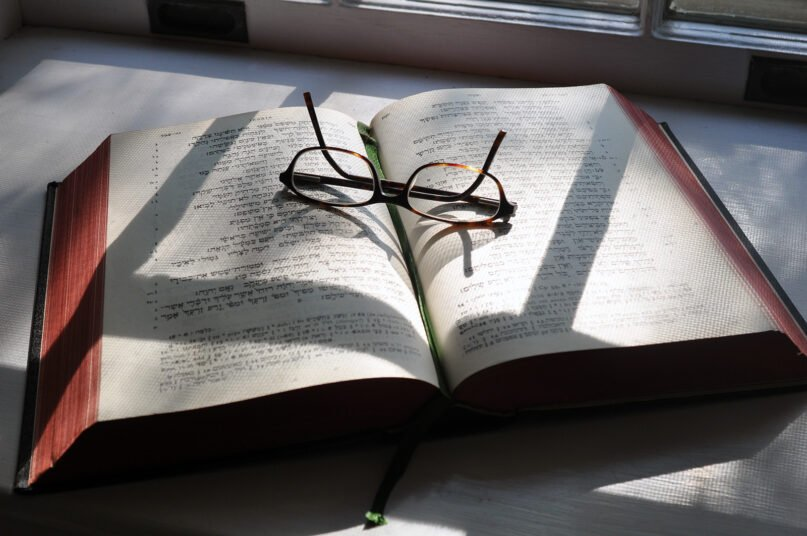 A pair of glasses sits on a Hebrew Bible. Photo by oskiles/Pixabay/Creative Commons