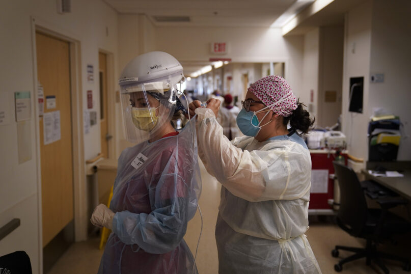 Registered nurse Dania Lima, right, helps fellow nurse Adriana Volynsky put on her personal protective equipment in a COVID-19 unit at Providence Holy Cross Medical Center in the Mission Hills section of Los Angeles on Dec. 22, 2020. (AP Photo/Jae C. Hong)