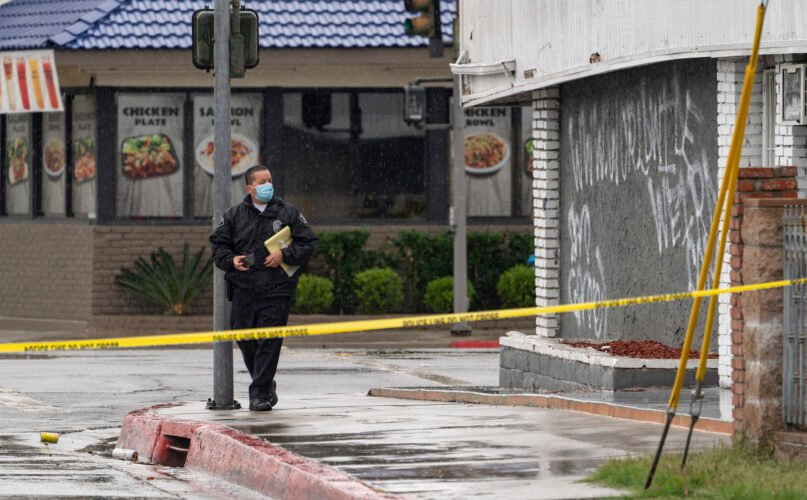 """El Monte Police Chief David Reynoso takes pictures of graffiti on the side wall of the First Works Baptist Church, after an explosion in El Monte, California, on Jan. 23, 2021. The church had been the target of protests for its anti-LGTBQ message. Officers noticed smoke coming from inside and realized a blast had blown the windows out. No injuries were reported. Protesters have repeatedly targeted the church headed by Pastor Bruce Mejia, who has condemned same-sex relationships. A statement on the church website calls homosexuality """"an abomination."""" Calls to the church went unanswered Saturday. (AP Photo/Damian Dovarganes)"""