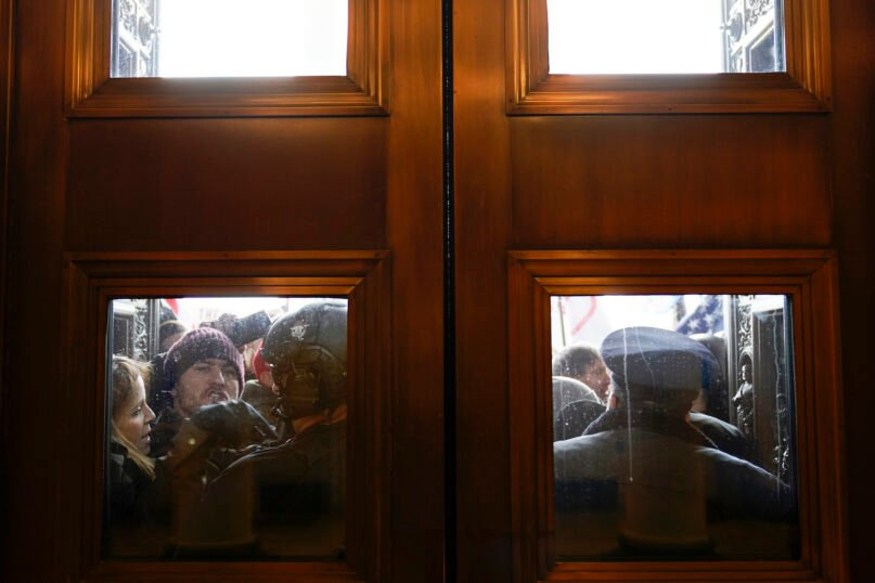 U.S. Capitol Police try to hold back protesters outside the east doors to the House side of the U.S. Capitol, Wednesday, Jan. 6, 2021. (AP Photo/Andrew Harnik)