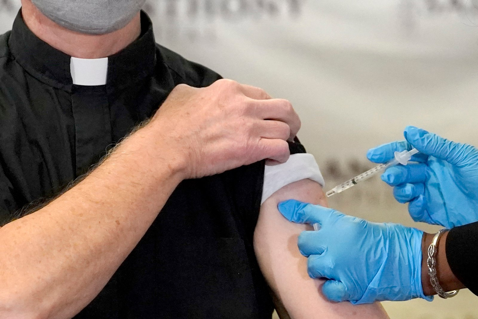 The Rev. Donald Nevins, pastor of St. Agnes of Bohemia Catholic Church in Chicago, left, receives the first of the two Pfizer-BioNTech COVID-19 vaccinations Dec. 23, 2020. (AP Photo/Charles Rex Arbogast)