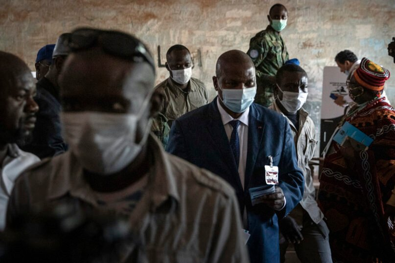 President Faustin-Archange Touadera, center right, arrives to cast his vote at the Lycee Boganda polling station in the capital, Bangui, Central African Republic, Dec. 27, 2020. (AP Photo)