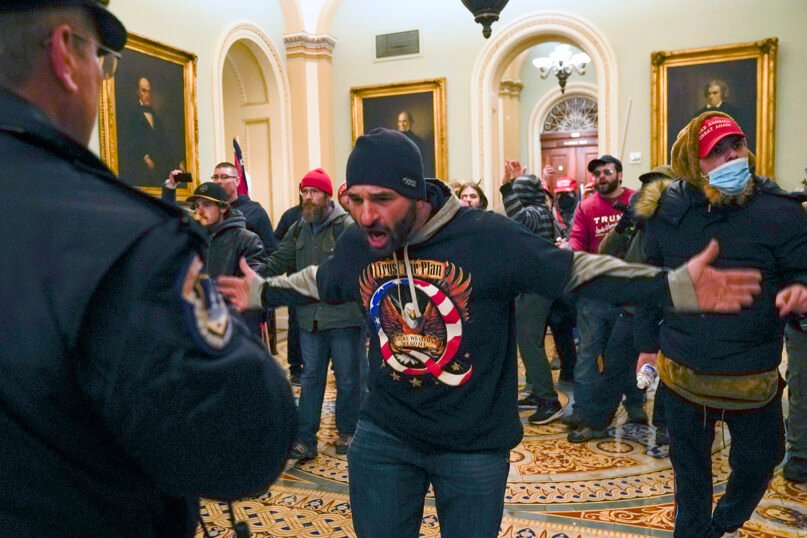 In this Jan. 6, 2021, file photo, Trump supporters, including Doug Jensen, center, confront U.S. Capitol Police in the hallway outside of the U.S. Senate chamber at the Capitol in Washington. (AP Photo/Manuel Balce Ceneta, File)