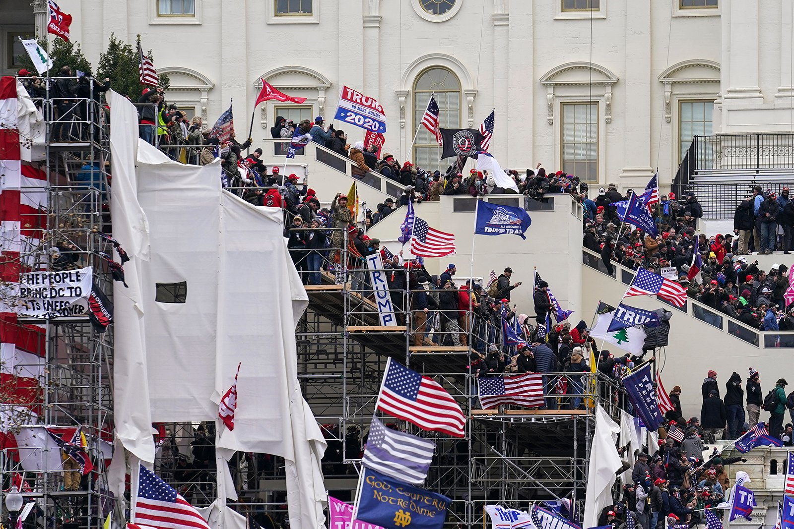 Trump supporters climb inauguration scaffolding outside the Capitol on Jan. 6, 2021, in Washington. (AP Photo/John Minchillo)