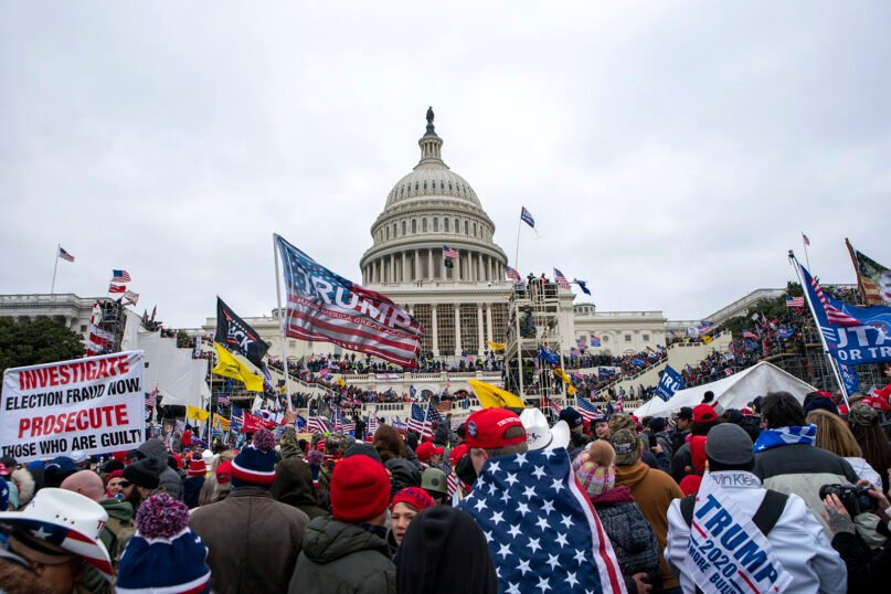 Supporters of President Donald Trump overtake the inauguration stage in front of the U.S. Capitol on Jan. 6, 2021, in Washington. (AP Photo/Jose Luis Magana)