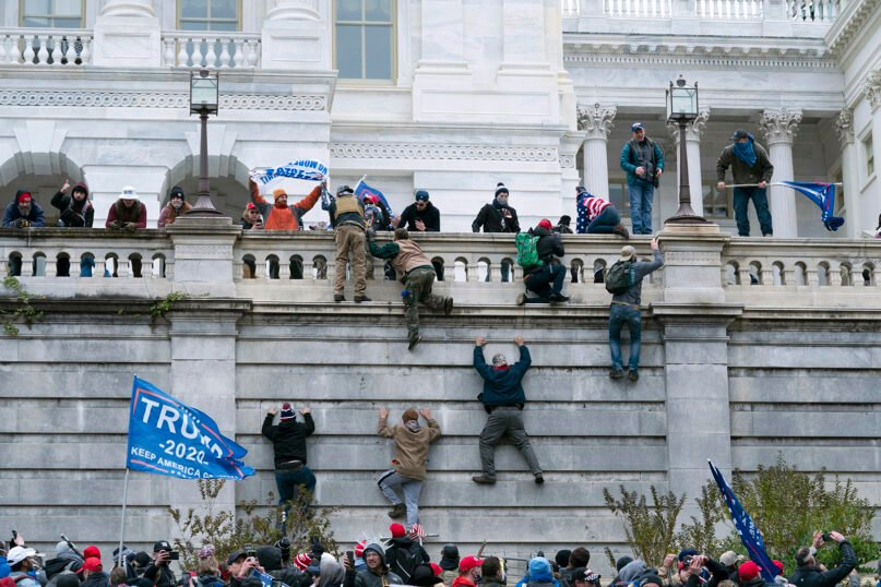 Supporters of President Donald Trump climb the west wall of the the U.S. Capitol on Jan. 6, 2021, in Washington. The mob proceeded to breach the Capitol. (AP Photo/Jose Luis Magana)