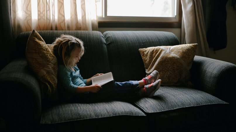 A child reads a Bible at home. Photo by Josh Applegate/Unsplash/Creative Commons