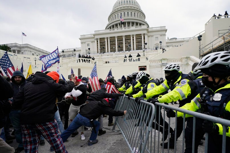 Trump supporters try to break through a police barrier on Jan. 6, 2021, at the Capitol in Washington. As Congress prepared to affirm President-elect Joe Biden's victory, thousands of people gathered to show their support for President Donald Trump and his claims of election fraud. (AP Photo/Julio Cortez)