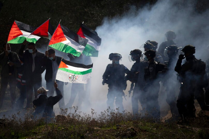 Israeli border police officers, right, and Palestinians clash during a Palestinian protest against the expansion of Israeli Jewish settlements near the West Bank town of Salfit, Thursday, Dec. 3, 2020. (AP Photo/Majdi Mohammed)
