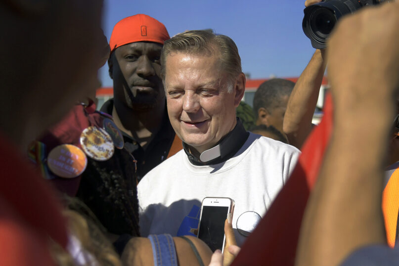 In this July 7, 2018, file photo, the Rev. Michael Pfleger, pastor of St. Sabina Catholic Church on Chicago's South Side, speaks to protesters before marching on the Dan Ryan Expressway in Chicago. In a letter written to the St. Sabina community, Chicago Cardinal Blase Cupich announced Jan. 5, 2021, that he has asked Pfleger to step aside from his ministry after receipt of a sexual abuse allegation of a minor by Pfleger more than 40 years earlier. (AP Photo/Annie Rice, File)