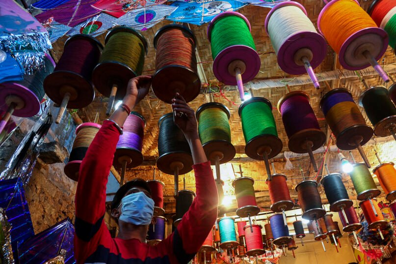 A vendor winds strings for kites ahead of the Hindu festival of Makar Sankranti, in Hyderabad, India, Sunday, Jan. 10, 2021. Kites are flown in many parts of India during the Hindu festival of Makar Sankranti, which marks the transition of winter to spring. (AP Photo/Mahesh Kumar A.)