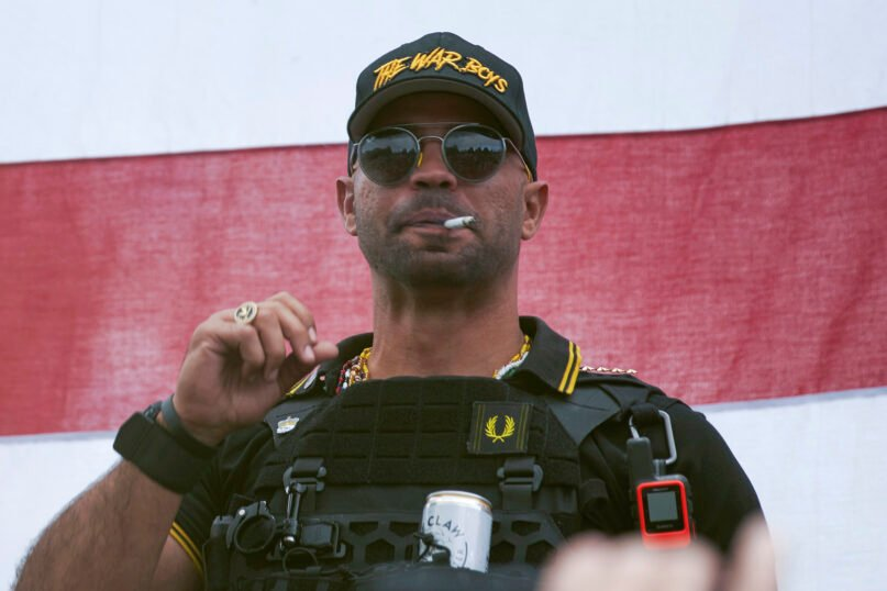 """In this Sept. 26, 2020, file photo, Proud Boys leader Henry """"Enrique"""" Tarrio wears a hat that says """"The War Boys"""" during a rally in Portland, Oregon. Police in the nation's capital on Jan. 4, 2021, arrested the leader of the Proud Boys, who is accused of burning a Black Lives Matter banner that was torn down from a historic Black church in downtown Washington in December 2020. (AP Photo/Allison Dinner, File)"""