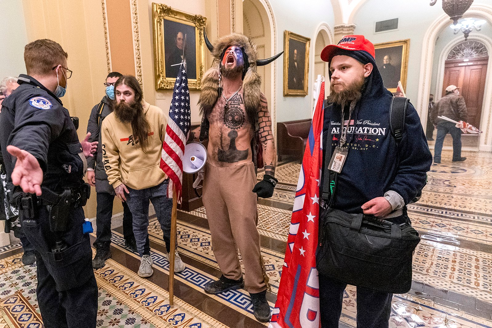 """Jake Angeli, center, better known as the """"QAnon Shaman,"""" and other supporters of President Donald Trump are confronted by Capitol Police officers outside the Senate Chamber inside the Capitol, Jan. 6, 2021, in Washington. (AP Photo/Manuel Balce Ceneta)"""