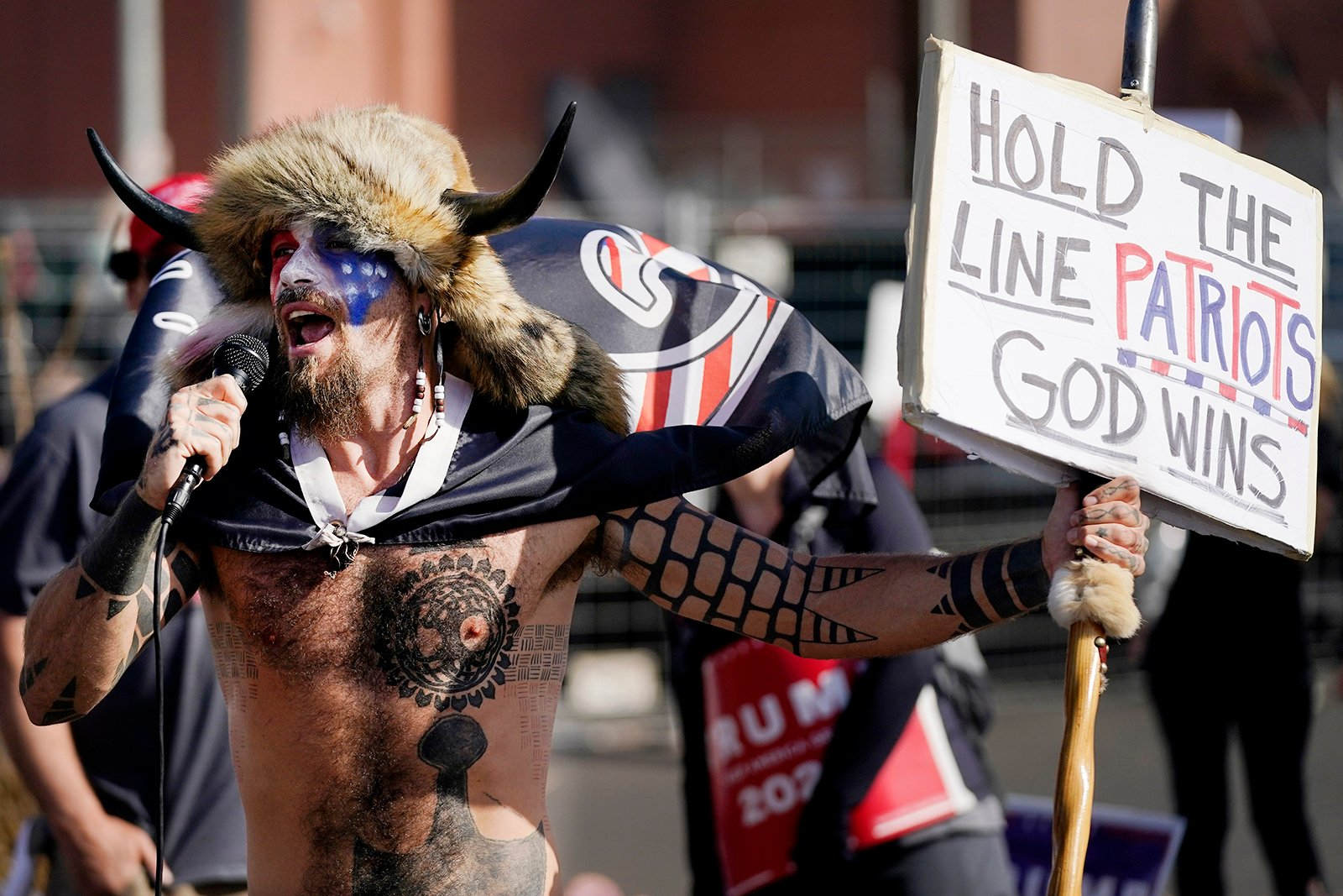 Jake Angeli, a supporter of President Donald Trump, speaks at a rally outside the Maricopa County Recorder's Office, Saturday, Nov. 7, 2020, in Phoenix. (AP Photo/Ross D. Franklin)