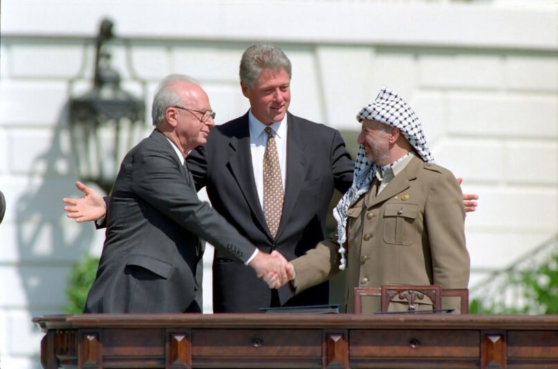 President Bill Clinton, center, looks on as Israeli Prime Minister Yitzhak Rabin, left, and PLO chairman Yasser Arafat share a famous handshake after the signing of the Oslo Accord at the White House on Sept. 13, 1993, in Washington. Photo by Vince Musi/The White House/Creative Commons