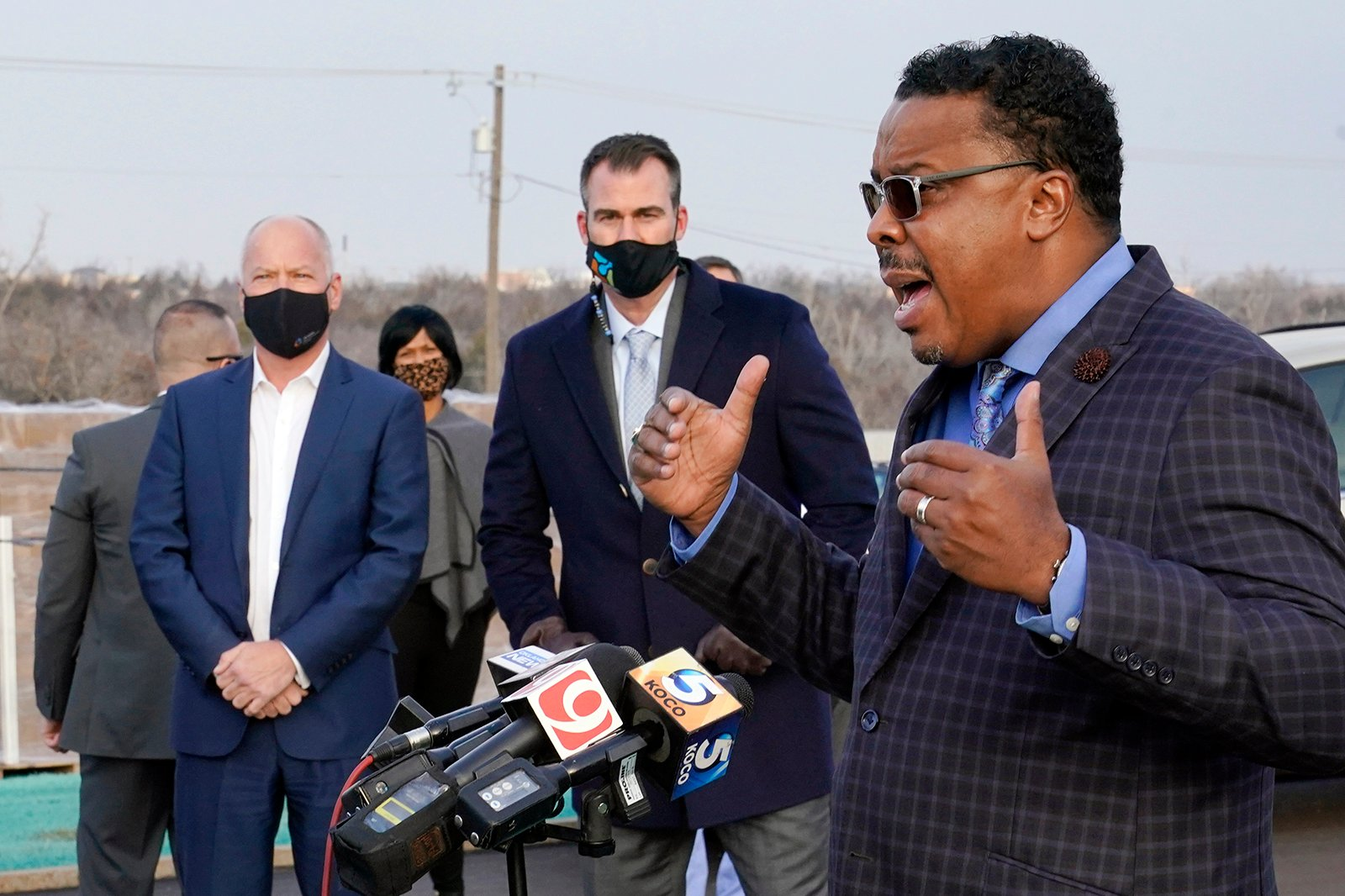 The Rev. Derrick Scobey, right, Ebenezer Baptist Church Senior Pastor, talks with the media as Oklahoma Gov. Kevin Stitt, center, and Dr. Lance Frye, left, State Commissioner of Health, look on, Tuesday, Jan. 26, 2021, in Oklahoma City. Scobey helped to organize the event in an effort to encourage more African Americans in Oklahoma City to receive the COVID-19 vaccine. (AP Photo/Sue Ogrocki)