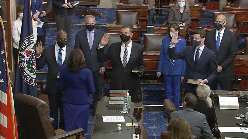 In this image from video, Vice President Kamala Harris swears in Sen. Raphael Warnock, D-Georgia, from left; Sen. Alex Padilla, D-California; and Sen. Jon Ossoff, D-Georgia, on the floor of the Senate, Jan. 6, 2021, on Capitol Hill in Washington. (Senate Television via AP)