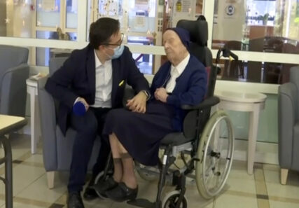 In this image made from BFM TV video, Sister Andre, born Lucile Randon, is interviewed by David Tavella, Communications Manager for the Sainte Catherine Laboure Nursing Home in Toulon, France, Tuesday Feb. 9, 2021. The nun is the second-oldest known living person in the world, according to the Gerontology Research Group, which validates details of people believed to be aged 110 or older. French media report that the nun tested positive for COVID-19 virus in mid-January but just three weeks later she is fit as a fiddle — albeit it in her regular wheelchair. (BFM TV via AP)