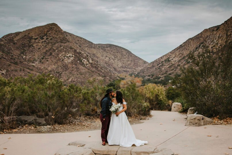 """In this Sunday, Dec. 27, 2020 photo provided by Kristen Pritchard Photography, Kayleigh and Cody Cousins pose for wedding photos at Mission Trails Regional Park in San Diego, Calif. They initially planned an April 2020 wedding, postponed it after the pandemic took hold, rescheduled it for December, then had to shift gears again when a new lockdown was imposed. """"That was devastating,"""" said Kayleigh. """"We said, 'Let's just do it on Zoom.'"""" (Kristen Pritchard Photography via AP)"""