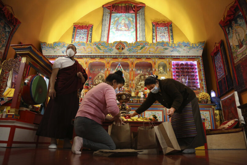 Lama Gelbu, left, Pasang Sherpa, center, and Yanddu Lama, right, prepare bags of fruit used as ceremonial offerings at the conclusion of the Dakini Day practice, a group meditationthat includessong and foodand iscelebrated on the 25thday of each lunar month, at the United Sherpa Association in the Queens borough of New York on Friday, Jan. 8, 2021. (AP Photo/Jessie Wardarski)