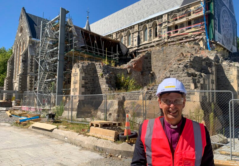 Peter Carrell, the Anglican bishop of Christchurch, outside the 2011 earthquake damaged Christ Church Cathedral in central Christchurch, New Zealand, Wednesday, Feb 11, 2021. The Christ Church Cathedral was arguably New Zealand's most iconic building before much of it crumbled during an earthquake 10 years ago. The years of debate that followed over whether the ruins should be rebuilt or demolished came to symbolize the paralysis that has sometimes afflicted the broader rebuild of Christchurch. But as the city on Monday marks one decade since the quake struck, killing 185 people and upending countless more lives, there are finally signs of progress on the cathedral. It's being rebuilt to look much like the original that was finished in 1904, only with modern-day improvements to make it warmer and safer. (AP Photo/Nick Perry)