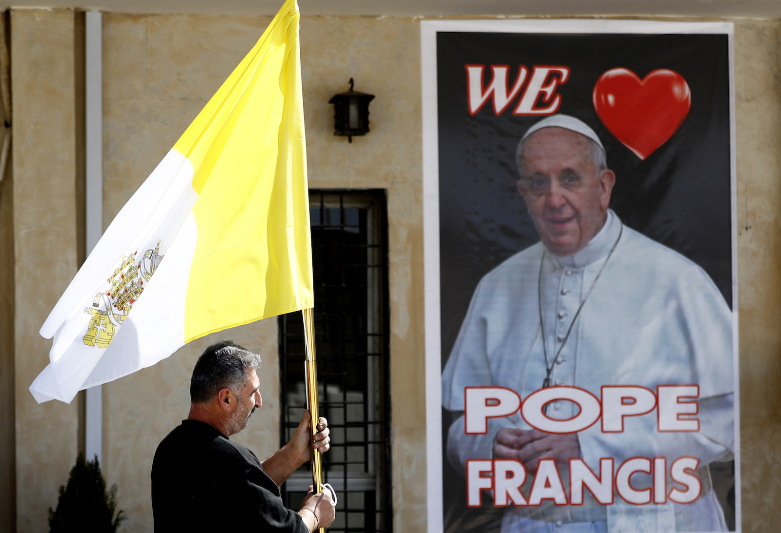 A Christian priest Places a poster of the Pope Francis and a Vatican flag during preparations for the Pope's visit in Mar Youssif Church in Baghdad, Iraq, Friday, Feb. 26, 2021. (AP/Photo/Hadi Mizban)