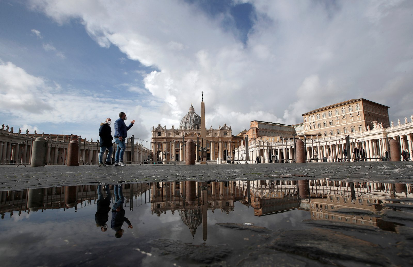 People are reflected on a puddle as they walk in an empty St.Peter's Square, at the Vatican, on Jan. 31, 2021. (AP Photo/Alessandra Tarantino)